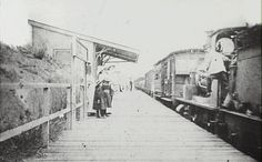 """Hazelbrook Station - Steam Engine hauling mixed train standing in station. Lady with three children waiting on platform. N.B. From Mr B. Schleicher, Hazelbrook: """"This is the original Hazelbrook Railway Station, opened in 1884. It was situated where the goods shed is now and was a single wooden platform. The present station was opened in April, 1902, when the section of duplicated track as far as Lawson was brought into use."""