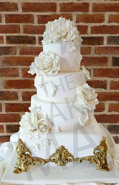 Elegant, traditional wedding cake with sugar flowers and an edible gold cake stand.