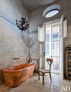 Serrano designed the master bath's tub, which was carved from local limestone and has Waterworks fittings; the chandelier dates from the 1920s.