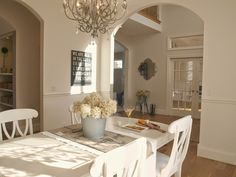 White shabby chic country dining room/white painted table and chairs/galvanized vase with dried hydrangea/silver chandelier/archways/Nordic French style/Hello Lovely Studio