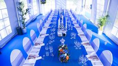 Een prachtige shot van boven van een ingedekte tafel voor een diner met een mega blauwe tafelloper, wijnglazen, kandelaars, bloemstukken en een gepersonaliseerde menukaart.