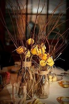 Colored roses with branches in jars make simple and beautiful centerpieces. Im also picturiny colored jars wit white!