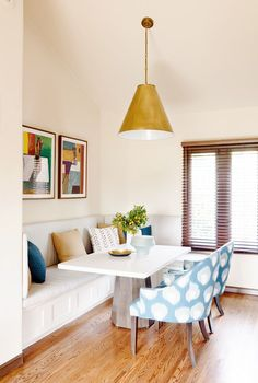 Brass and blue breakfast nook with abstract art, industrial lighting, and many pillows