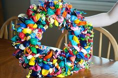 Birthday wreath: 8 bags of 25count balloons from Dollar store, lots of craft pins (.99 cents at Walmart for 100 ct.), curly ribbon and wreath! Easy peasy!