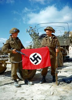 Canadian troops posing with a captured German flag, near Hautmesnil, France, 10 Aug 1944; note Sten gun and Lee-Enfield rifle. (Library and Archives Canada)