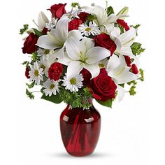 Add some romance to the holiday season with this rich arrangement of luxurious flowers in classic winter colors. Red roses, snow white lilies and playful daisies are gathered in a ruby red vase she'll use well beyond Christmas!