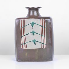 HAMADA SHINSAKU Bottle Vase, Stoneware, layered green over brown glazes, a cream panel front and back with 'Okinawa' style geometric design in red and green overglaze enamel, together with a signed wooden Box, H 22cm, W 16cm, D 8.5cm