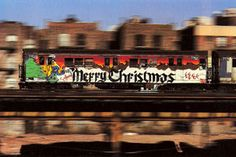 A Merry Christmas reminder sent from 1985 on a New York subway train. Painted by Lyndah and P Jay. Caught racing along by photographer Martha Cooper.