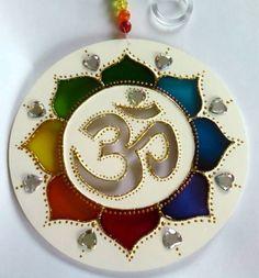 Mandala em acrílico de 15cm de diâmetro,pintura em vitral, decorada com tinta relevo dourada e pedrinhas acrílicas em ambos os lados.       Om (?) é o mantra mais importante do hinduísmo e outras religiões. Diz-se que ele contém o conhecimento dos Vedas e é considerado o corpo sonoro do Absoluto....