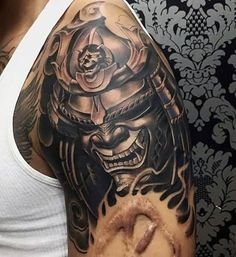 Black Ink Samurai Head Tattoo On Man Left Shoulder