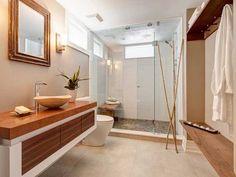 Une salle de bain ambiance zen et naturelle associe banc et plan vasque en bois à un parterre de douche à l'italienne en galets et des joncs de bambous