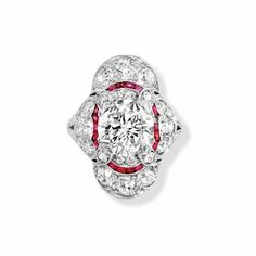 Diamond and Ruby Ring   Platinum, centering one old European-cut diamond approximately 1.80 cts., framed by 4 small old European-cut diamonds, quartered by diamond-set ribbons, further edged by numerous French-cut rubies, accented by 4 curved panels set with 8 old European-cut and 16 small old-mine cut diamonds, approximately 1.40 cts., circa 1915
