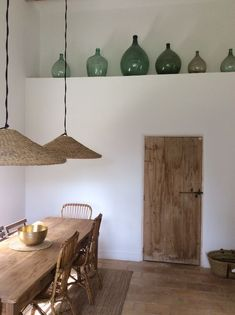 Rustic decor in a farmhouse dining area with green wine bottle jug collection, wicker pendant lights, farm table, and wood door.