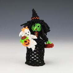 """Fabulous witch carrying a baby ghost with a Jack O'lantern and a broom. Hand beaded by Andrea Laahty. Unique Native American beadwork that will be a great addition to any collection. 3 3/8"""" tall x 2 1/2"""" long x 2 1/8"""" wide Artist card included"""