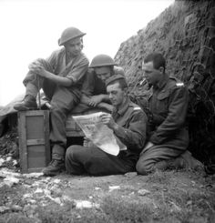"""Fred Morris, Ed Lacey, Maurice Luftspring and George Mutcheon read a copy of """"The Maple Leaf"""", printed at the Caron printing works, Rue Demolombe, Caen, for troops of the Canadian army serving in France. It was printed once a week and was the broad equivelent of the US """"Stars and Stripes"""". The soldiers appear to be members of the 2nd Canadian Infantry Division. The soldier on his knees appears to be a motorcyclist judging by his boots and trousers."""