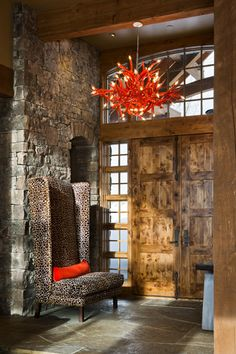Interior Entry with stone wall, rustic wood doors, dramatic high back wing chair... love the red chandelier. (Locati Architects & Interior Designs).