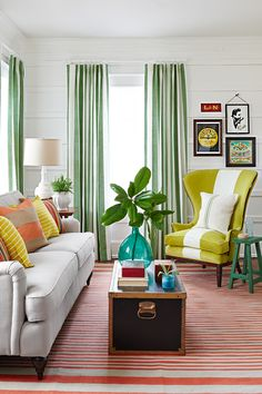 "Here, 1"" x 4"" pine boards, spaced about a foot apart, offer the look of custom paneling at a fraction of the price. Curtains in narrow vertical stripes break up the wall's horizontal lines. Multi-stripe pillows in complementary hues band together to dress up a neutral sofa. A wide white stripe, applied to the armchair's center using fabric paint (available at craft stores), packs a graphic punch.   - CountryLiving.com"