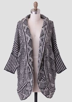 This ultra-soft cardigan features a marled geometric design in hues of black and beige with fitted dolman sleeves. Perfected with a darling tulip-cut hem at the back, this cozy cardigan styles we...
