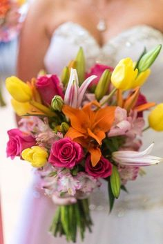 Vibrant tiger lily bouquet with hot pink roses, bright yellow tulips, orange tiger lilies and light pink peruvian lilies. Summer bridal bouquet.