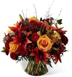 Warm Beauty Bouquet. Orange roses, Asiatic lilies, burgundy carnations, mini carnations, red matsumoto asters, red hypericum berries, and a variety of lush greens arranged with birch branches in a clear glass bubble bowl vase.