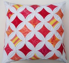 Hand-quilted cathedral window pillow with a red orange batik motif by warmfuzzies on etsy. She has an nice selection of colors & gives her pillows a modern twist by only using the pattern in the center. One of my very favorite quilt patterns!