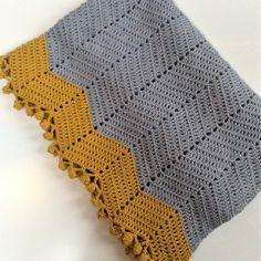 Minimalistic and beautiful crochet baby blanket in ripple pattern - chevron pattern - with a simplistic Nordic feel - for baby boys and girls. The pompon edging makes all the difference!!  Read more - denpudredeugle.wordpress.com/2019/08/21/uglens-babytaeppe-balance/