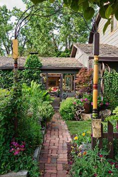 secret garden on urban plot street entrance to house with brick walkway, trellis and arch