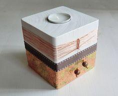 Teelichthalter aus Holz mit weißer Lacklasur (Speichelecht) und mit braunem Band und Blattmetall beklebt. Verziert mit Bronzedraht und Perlen. Incl. Teelicht.  Die Farben können auf Grund...