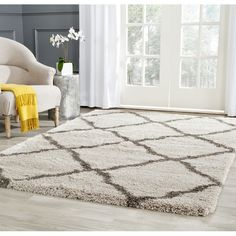 Abstracted from a tribal motif, this rug is crafted with undulating geometric motif in grey on a taupe ground. Power-loomed of easy care polypropylene yarn, this plush shag is crafted with a deep, dense pile for luxury underfoot.
