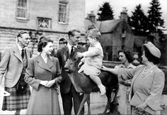 Prince Charles is center of attention as he sits astride the sculpture of a deer during a family gathering at Balmoral Castle, Scotland. August 1951.