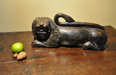 A LATE 16TH/ EARLY 17TH CENTURY CARVING IN ASH OF A RECUMBENT LION. CIRCA 1600.