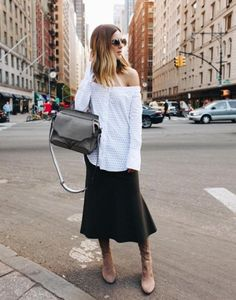 An off-the-shoulder oversize shirt over a full skirt and knee-high boots.