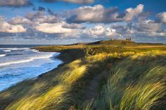 Northumbria at its best : clouded skies, a desolate beach and an impressive castle overlooking northumberland