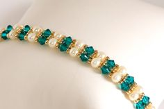 Delicate bracelet beadwoven in blue zircon (teal) Swarovski Elements crystals, cream glass pearls, and 22kt gold-plated seed beads. Perfect for prom, or how about for a bridesmaid? Blue zircon is one of the birthstones for December. Securely woven with 6 lb crystal Fireline. This bracelet is 6 3/4 inches long (including gold-plated pewter toggle clasp) and 3/8 inch wide. Please measure your wrist carefully to be sure it will fit before ordering. I could possibly add a couple more...