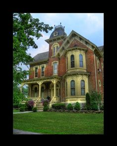 This serene house looks amazingly well-cared for.  Nice bays and center 4-story tower.  Love the brick.  The buttery yellow trim is nice but I would use another couple of colors to highlight some of the marvelous architectural detail.  Beautiful yard.
