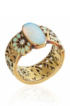 RENÉ LALIQUE - AN ART NOUVEAU OPAL, ENAMEL AND DIAMOND BAND RING, CIRCA 1900. Set with an oval cabochon opal, to the textured gold, enamel and diamond foliate band ring, mounted in gold, signed Lalique. #GoldJewelleryArtNouveau