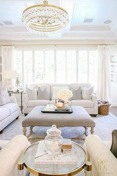 Neutral living room with square ottoman and white couches. Still a family friendly space! Transitional Family Room Reveal - Randi Garrett Design. Crystal and brass drop chandelier.