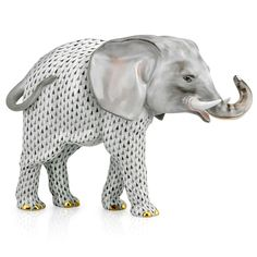"""A magnificently detailed porcelain elephant adorned with Herend's prized fishnet pattern in a striking blend of black and gray. Each piece of Herend porcelain giftware is a unique work of art brought to life by the skilled hands of artisans. The figurine has 24k gold accents and makes a unique collectible or distinctive gift. Measures 14 ½""""l x 10""""h x 6""""w. Handmade and handpainted in Hungary exclusively for Scully & Scully."""