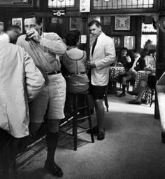 "1953. The above photo was part of a series of LIFE magazine photos around the rise of shorts. It was captioned: ""Patrons inside P.J. Clarke's saloon (in New York City) include men wearing shorts, a new fad."""