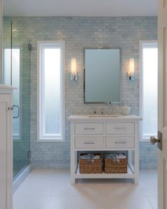 This gorgeous bathroom features a light, calming design. White and blue tile covers the walls, adding soft color to the room. A white vanity fits perfectly between two thin windows and echos the clean white of the floor and ceiling.
