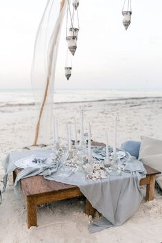 beach wedding picnic table with a light blue tablecloth, shells and candles