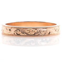 This antique inspired wedding band is handcrafted in 14k rose gold. Hand engraved scroll patterns extend along the entire band for a continuous look. Milgrain texture is applied to the edges of the design to add dimension and complete its vintage appeal.  http://www.knoxjewelers.biz/products/scroll-engraved-band-4-mm