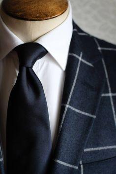 Ceinture : cuir noir. Chaussettes : Falke cachemire bleue. Chemise : Van Laak blanche. Costume : Wicket windowpane bleue. Cravate : Puccini bleue. Lunettes : Rayban Wayfarer noire. Montre : IWC noire. Pochette : soie blanche. Souliers : Finsbury noire bout fleuri.