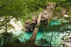 A hanging bridge and a hiker over Soča river, Bovec, Slovenia