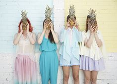 Four models in pastel coloured clothing hold pineapples in front of their faces in a tropical photo shoot by Victoria Siddle for DIYcouture