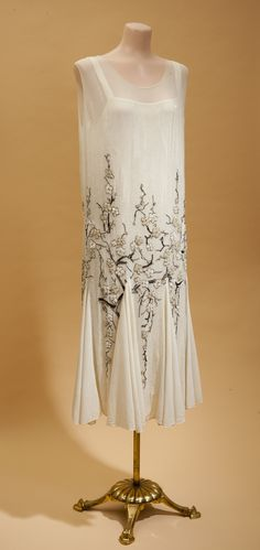 Mid-late '20s ivory silk crepe with beaded design of flowering branches against a background of clear bugle beads. Plain triangular panels in the skirt add textural contrast and movement.