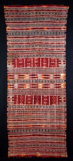 Africa | This mushtia shawl is from Jbiniana, a village between Sfax and Mediha, in Tunisia. |  Spots of orange henna accent the complex bands of white, black and red wool. | Early to mid-20th century.