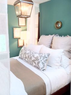teal walls, lantern light, natural bedding (linen), tiny round mirror, gilver framed book pages