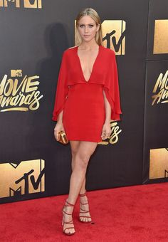 Un vestido de color rojo con capa y acentuado escote fue la apuesta de Brittany Snow. El diseño es de Haney.