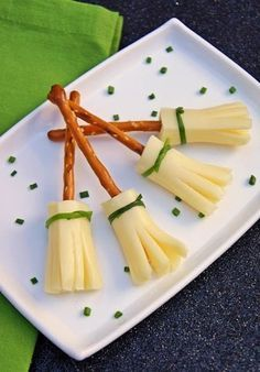 Cheese brooms. Looks like 1/3 or 1/2 of a cheese snack stick with one end snipped using a knife of kitchen shears then insert a pretzel stick in other end. Perhaps chive tied around the broom... Adorable!